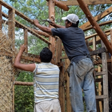 Marcos and Marlon building El Piscacho Study Center walls with straw, timber and metal wires.